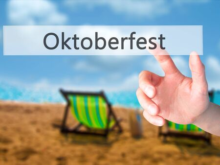 Oktoberfest - Hand pressing a button on blurred background concept . Business, technology, internet concept. Stock Photo
