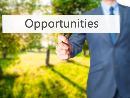 Opportunities - Businessman hand holding sign. Business, technology, internet concept. Stock Photo