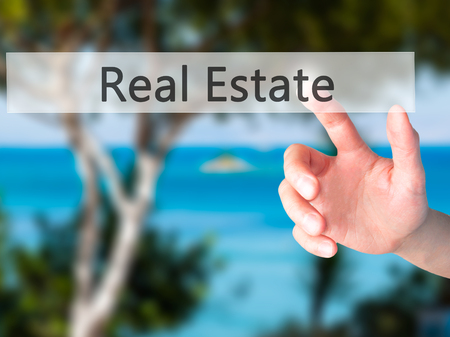 Real Estate - Hand pressing a button on blurred background concept . Business, technology, internet concept. Stock Photo