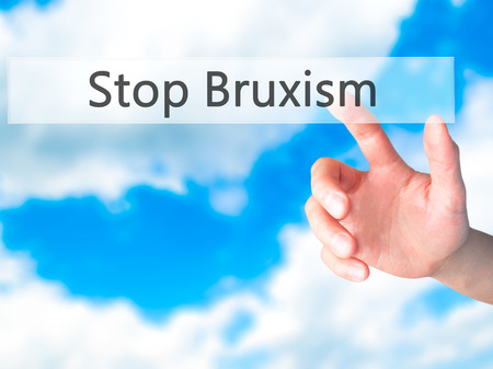Stop Bruxism - Hand pressing a button on blurred background concept . Business, technology, internet concept. Stock Photo