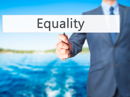 invalidity: Equality - Businessman hand holding sign. Business, technology, internet concept. Stock Photo Stock Photo