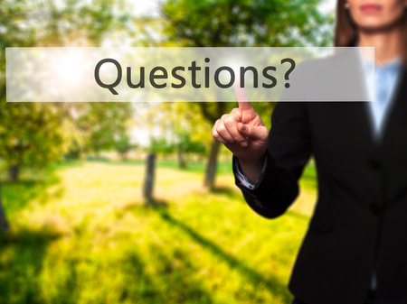 Questions ? - Isolated female hand touching or pointing to button. Business and future technology concept. Stock Photo