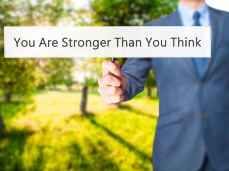 stronger: You Are Stronger Than You Think - Businessman hand holding sign. Business, technology, internet concept. Stock Photo