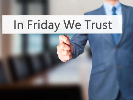 positiveness: In Friday We Trust - Businessman hand holding sign. Business, technology, internet concept. Stock Photo