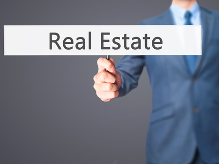 finer: Real Estate - Businessman hand holding sign. Business, technology, internet concept. Stock Photo