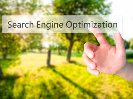 meta tags: Search Engine Optimization - Hand pressing a button on blurred background concept . Business, technology, internet concept. Stock Photo