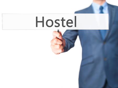 hostel: Hostel - Businessman hand holding sign. Business, technology, internet concept. Stock Photo Stock Photo