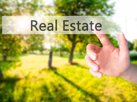 finer: Real Estate - Hand pressing a button on blurred background concept . Business, technology, internet concept. Stock Photo