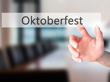 prost: Oktoberfest - Hand pressing a button on blurred background concept . Business, technology, internet concept. Stock Photo