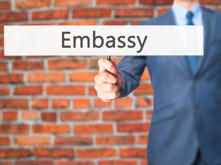 Embassy - Businessman hand holding sign. Business, technology, internet concept. Stock Photo