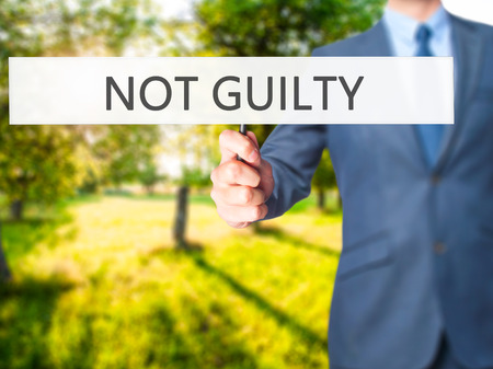 white backing: NOT GUILTY - Business man showing sign. Business, technology, internet concept. Stock Photo Stock Photo