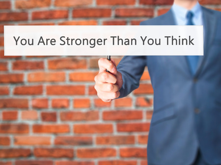 You Are Stronger Than You Think - Businessman hand holding sign. Business, technology, internet concept. Stock Photo