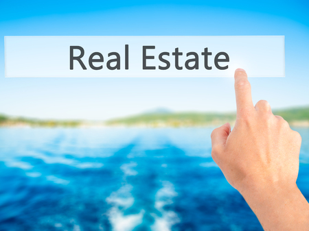 low price: Real Estate - Hand pressing a button on blurred background concept . Business, technology, internet concept. Stock Photo