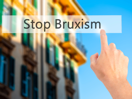 grinding teeth: Stop Bruxism - Hand pressing a button on blurred background concept . Business, technology, internet concept. Stock Photo