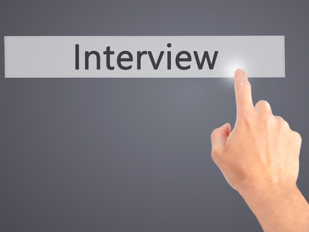 new recruit: Interview - Hand pressing a button on blurred background concept . Business, technology, internet concept. Stock Photo
