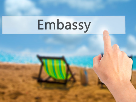Embassy - Hand pressing a button on blurred background concept . Business, technology, internet concept. Stock Photo