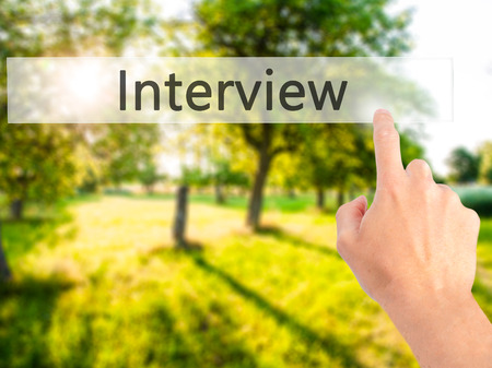 Interview - Hand pressing a button on blurred background concept . Business, technology, internet concept. Stock Photo