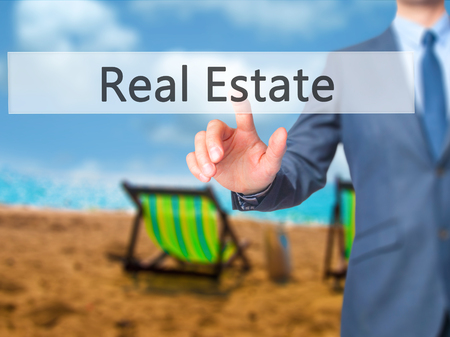 finer: Real Estate - Businessman click on virtual touchscreen. Business and IT concept. Stock Photo