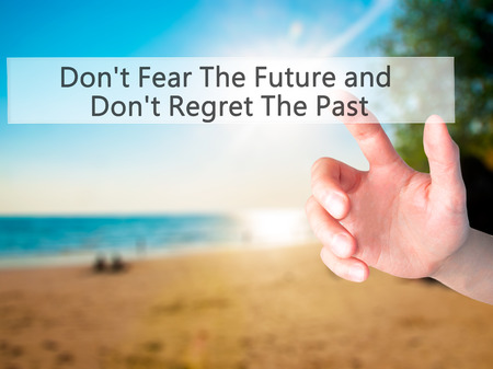 Dont Fear The Future and Dont Regret The Past - Hand pressing a button on blurred background concept . Business, technology, internet concept. Stock Photo Stock Photo