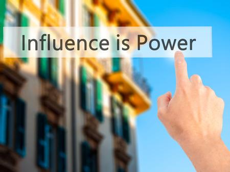 magnetismo: L'influenza è potere - Mano premendo un pulsante su sfondo sfocato concetto. Affari, tecnologia, il concetto di internet. Archivi fotografici