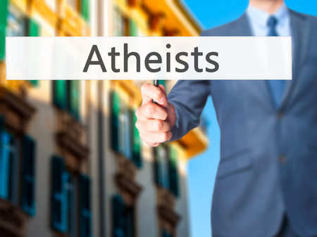 atheism: Atheists - Businessman hand holding sign. Business, technology, internet concept. Stock Photo Stock Photo