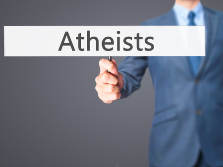 atheist: Atheists - Businessman hand holding sign. Business, technology, internet concept. Stock Photo Stock Photo
