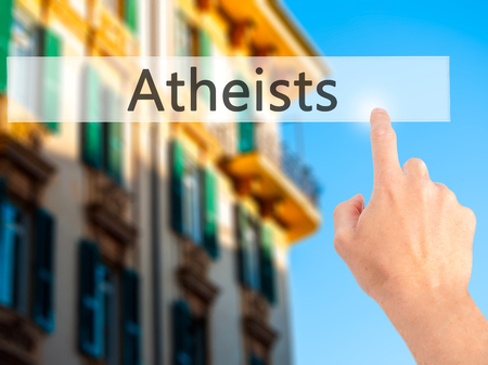Atheists - Hand pressing a button on blurred background concept . Business, technology, internet concept. Stock Photo Stock Photo