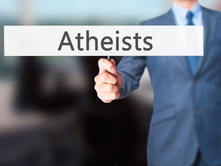 nonbelief: Atheists - Businessman hand holding sign. Business, technology, internet concept. Stock Photo Stock Photo