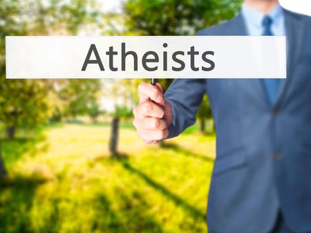 criticism: Atheists - Businessman hand holding sign. Business, technology, internet concept. Stock Photo Stock Photo