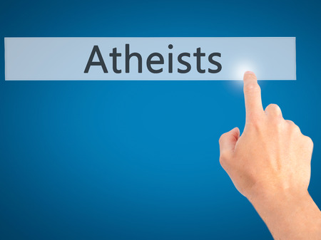atheist: Atheists - Hand pressing a button on blurred background concept . Business, technology, internet concept. Stock Photo Stock Photo
