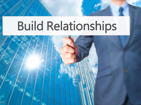 middleman: Build Relationships - Businessman hand holding sign. Business, technology, internet concept. Stock Photo