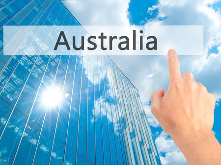 Australia - Hand pressing a button on blurred background concept . Business, technology, internet concept. Stock Photo