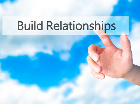 trustful: Build Relationships - Hand pressing a button on blurred background concept . Business, technology, internet concept. Stock Photo