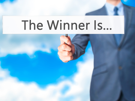 medalist: The Winner Is... - Businessman hand holding sign. Business, technology, internet concept. Stock Photo
