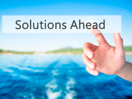 Solutions Ahead - Hand pressing a button on blurred background concept . Business, technology, internet concept. Stock Photo