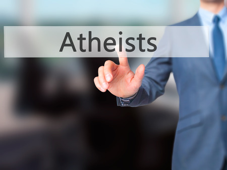 disbelieve: Atheists - Businessman hand pressing button on touch screen interface. Business, technology, internet concept. Stock Photo