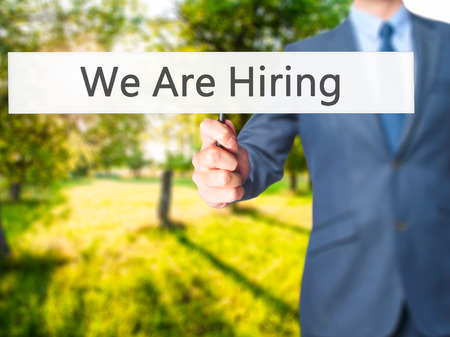 We Are Hiring - Businessman hand holding sign. Business, technology, internet concept. Stock Photo