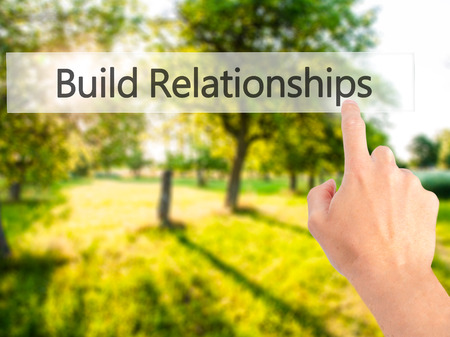 intercessor: Build Relationships - Hand pressing a button on blurred background concept . Business, technology, internet concept. Stock Photo