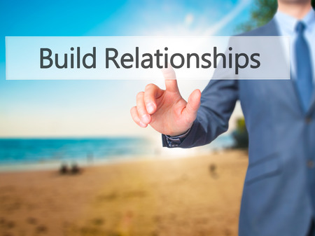Build Relationships - Businessman hand pressing button on touch screen interface. Business, technology, internet concept. Stock Photo