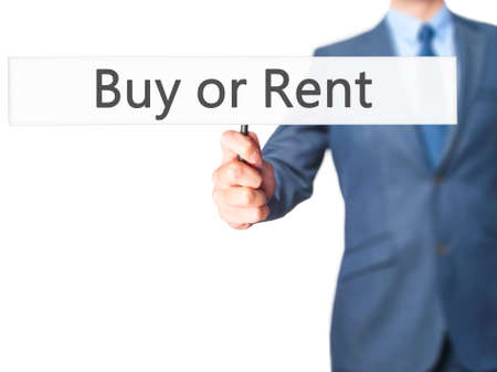 buying questions: Buy or Rent - Business man showing sign. Business, technology, internet concept. Stock Photo