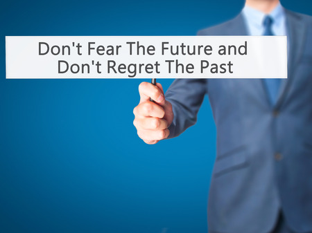 regret: Dont Fear The Future and Dont Regret The Past - Businessman hand holding sign. Business, technology, internet concept. Stock Photo