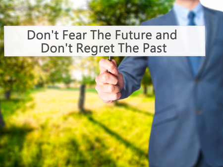 Dont Fear The Future and Dont Regret The Past - Businessman hand holding sign. Business, technology, internet concept. Stock Photo