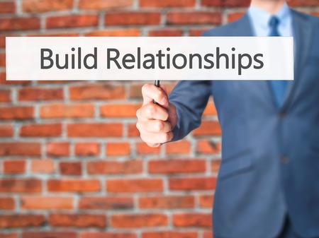 intercessor: Build Relationships - Businessman hand holding sign. Business, technology, internet concept. Stock Photo