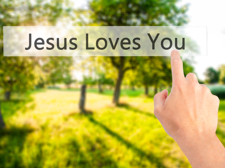testament schreiben: Jesus Loves You - Hand pressing a button on blurred background concept . Business, technology, internet concept. Stock Photo