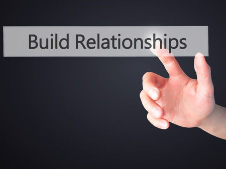 Build Relationships - Hand pressing a button on blurred background concept . Business, technology, internet concept. Stock Photo