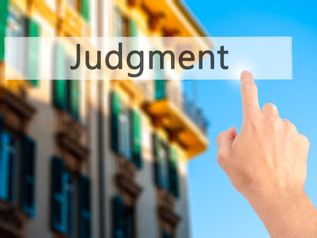 judgment: Judgment - Hand pressing a button on blurred background concept . Business, technology, internet concept. Stock Photo