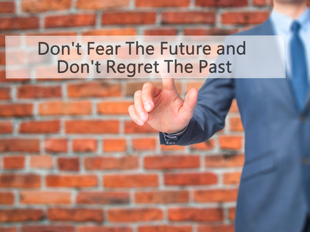 Dont Fear The Future and Dont Regret The Past - Businessman hand pressing button on touch screen interface. Business, technology, internet concept. Stock Photo Stock Photo