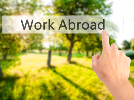 Work Abroad - Hand pressing a button on blurred background concept . Business, technology, internet concept. Stock Photo