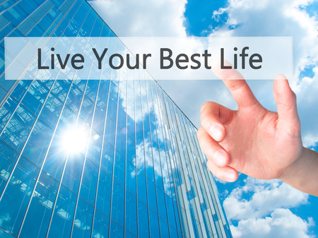 personal perspective: Live Your Best Life - Hand pressing a button on blurred background concept . Business, technology, internet concept. Stock Photo