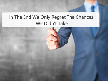 regret: In The End We Only Regret The Chances We Didnt Take - Businessman hand holding sign. Business, technology, internet concept. Stock Photo Stock Photo
